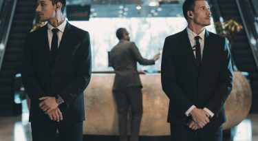 Two,Bodyguards,Waiting,For,Businessman,Standing,At,Reception,Counter